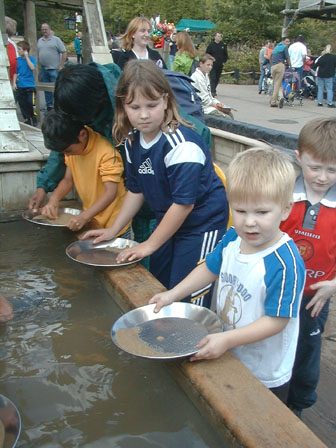 Beverley & Howard panning for gold, with Danny looking on