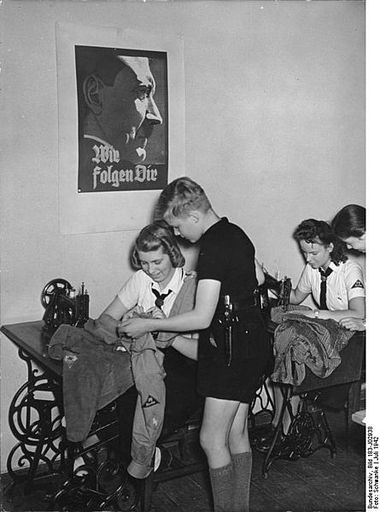 """1942 - BDM girls learning how to sew. Poster reads: """"We follow You"""""""
